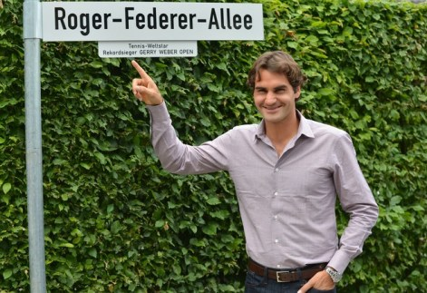 Swiss tennis player Roger Federer poses by a street sign reading his name near the Gerry Weber Stadium in the city of Halle western Germany on June 11, 2012 where the Halle ATP open started today. Federer has won the tournament five times. AFP PHOTO / CARMEN JASPERSENCARMEN JASPERSEN/AFP/GettyImages