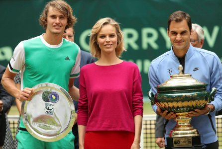HALLE: Switzerland's Roger Federer, right, with the winner trophy and Germany's Alexander Zverev, left, with the trophy for the second place, frame model Eva Herzigova, after the final match of the Gerry Weber Open tennis tournament in Halle, Germany, Sunday, June 25, 2017. AP/PTI(AP6_25_2017_000167B)